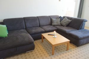 Wohnzimmer. Großzügiges Sofa, das sich für zwei Personen zum Doppelbett umbauen lässt.