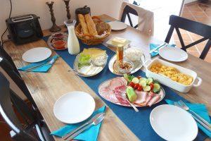 Brötchen, Baguette, ein Ei (wahlweise Rüherei), Butter, Käse, Wurst, Honig/Marmelade oder Nutella, eine Kanne Kaffe oder Tee, Milch.
