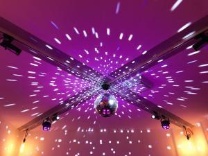 Tanzfläche. Beleuchtung mit Retro-Glühlampen, farbigen Strahlern und Disco-Kugel.